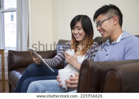 Chinese couple relaxing together at home with tablet computer. Happy young Asain couple sitting on a sofe together having fun using Digital Tablet PC. - stock photo