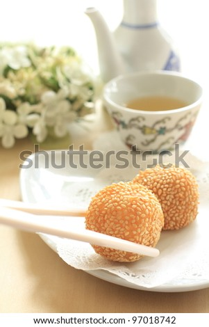 Chinese cuisine, sesame deep fried dim sum with tea and flower - stock photo