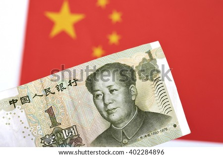 Chinese currency in front of a Chinese flag - stock photo