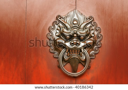 Chinese decoration of bronze lion on the red wall.