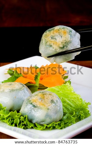 Chinese Dim Sum dumpling being held by chopsticks - stock photo