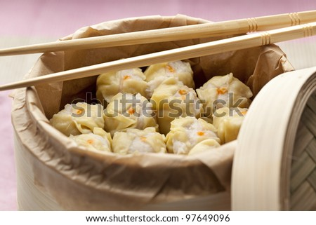 Chinese Dim Sum in a steaming basket with chopsticks - stock photo