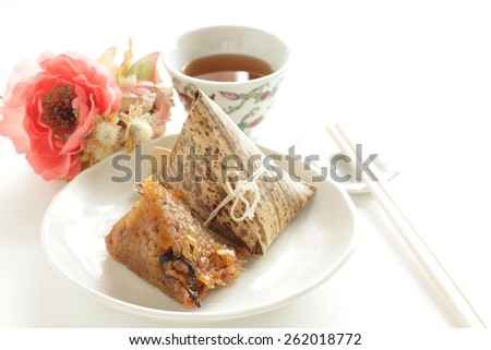 chinese dim sum, Zongzi in Japanese style with black tea on background - stock photo