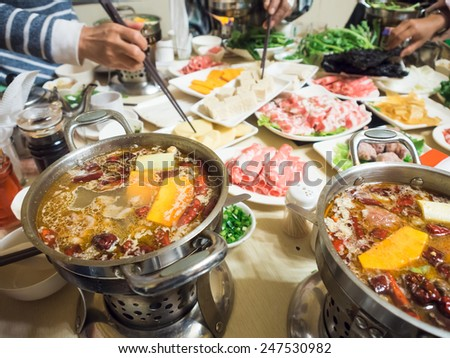 Chinese dinning dip sliced meat in chilli hot soup with chopsticks, shabu shabu - stock photo