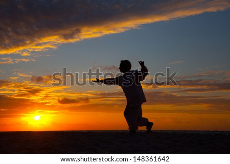 Chinese Elderly Woman Performing Taichi Outdoor by the beach under sunset sunrise silhouette - stock photo