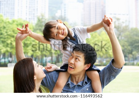 Chinese Family Giving Daughter Ride On Shoulders In Park - stock photo