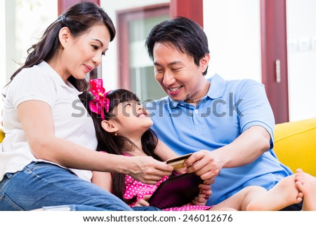 Chinese family online shopping with tablet computer and credit card - stock photo