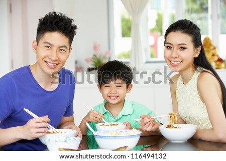 Chinese Family Sitting At Home Eating A Meal