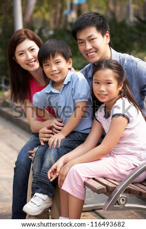 Chinese Family Walking Sitting On Bench In Park Together - stock photo
