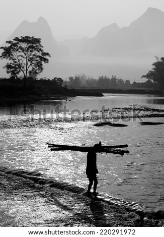 Chinese farmer crossing a river with bamboo sticks, Guilin, Guangxi.  - stock photo