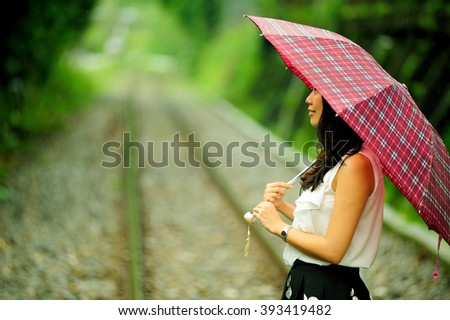 Chinese girl standing on railway track with green forest background in the rain,taiwan. - stock photo