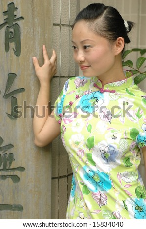 Chinese girl wearing traditional dress, standing next to wooden pillar with Chinese characters.