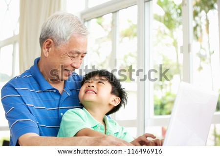 Chinese Grandfather And Grandson Sitting At Desk Using Laptop At Home - stock photo