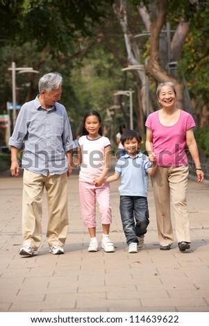 Chinese Grandparents Walking Through Park With Grandchildren - stock photo