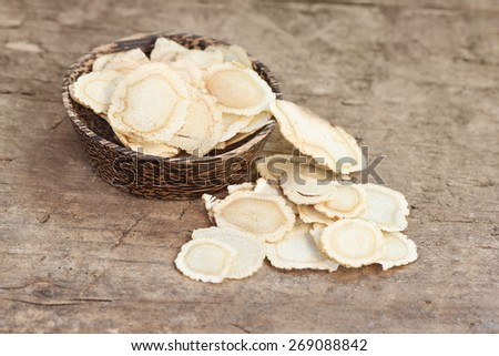 Chinese Herbal medicine - American Ginseng slices (Panax quinquefolius) in a bowl on wooden board (manual focus) - stock photo