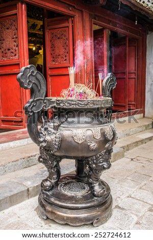Chinese joss-stick pot in front of red door of chinese temple in Hanoi, Vietnam