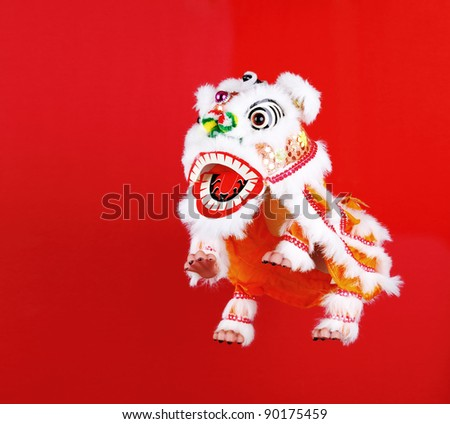 Chinese lion dance head decoration over red background. Space for text. - stock photo