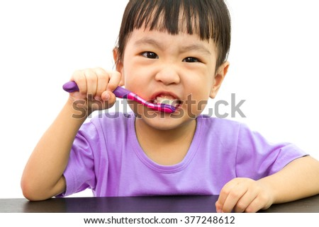 Chinese little girl brushing teeth in plain white isolated background. - stock photo
