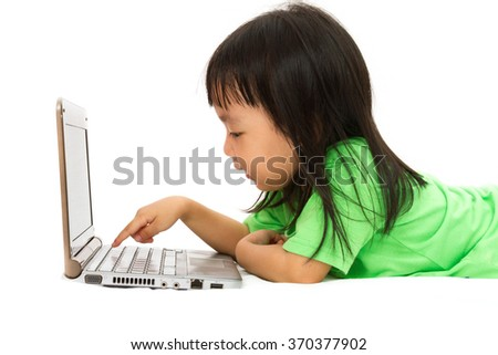 Chinese little girl lying down with laptop in plain white isolated background.