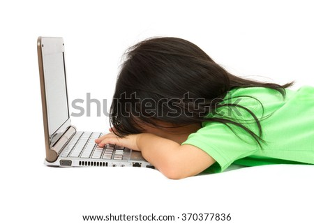 Chinese little girl sleep in front of a laptop in plain isolated white background. - stock photo