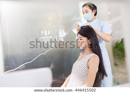 chinese long-haired girl with professional hairdressers use the tester to test skin girl