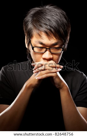 Chinese male adult contemplate in dark background - stock photo