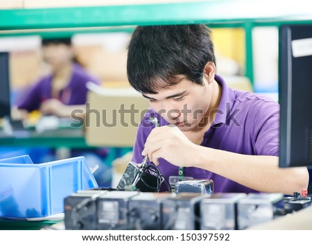 chinese male worker assembling production at line conveyor in china factory - stock photo