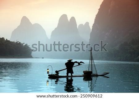 Chinese man fishing with cormorants birds in Yangshuo, China - stock photo