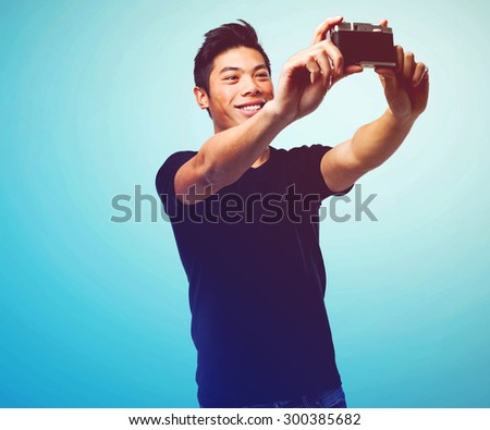 chinese man taking a selfie with camera - stock photo