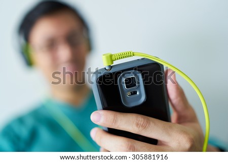 Chinese man watching podcast on mobile phone, listening with green big earphones. Copy space and selective focus on cable - stock photo