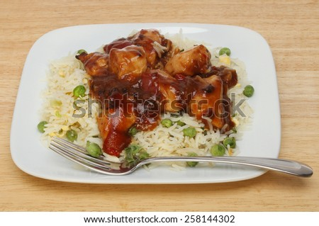 Chinese meal, chicken in black bean sauce with rice on a plate with a fork - stock photo