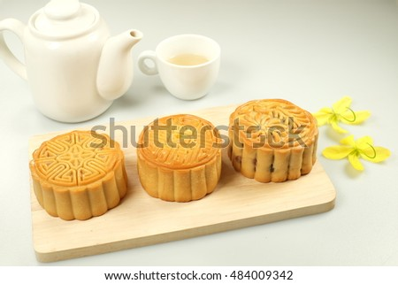 Chinese mid autumn festival foods. Traditional mooncakes on table setting with teacup.