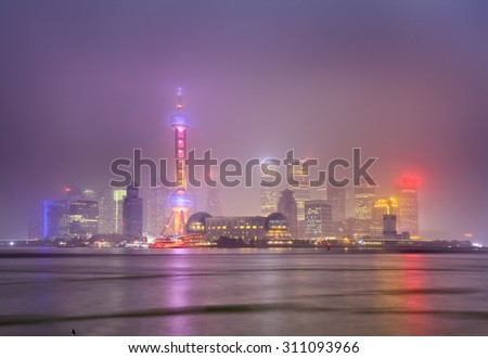 Chinese modern megapolis Shanghai - view at sunset towards Pudong brightly illuminated by lights with reflection in Yangtze river - stock photo