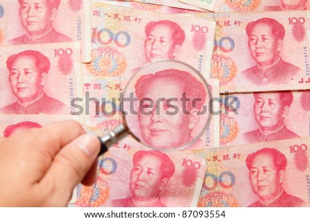 chinese money (currency) and magnifying glass, concept for finance issue - stock photo
