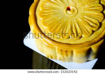 Chinese Moon cake on black background, the Chinese words on the mooncake means yolk.   - stock photo