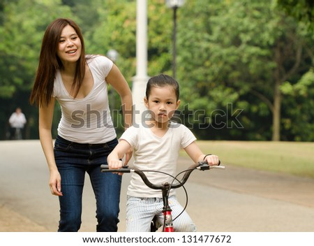 chinese mother teaching her daughter riding bicycle outdoor - stock photo
