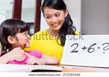 Chinese mother teaching mathematics to child - stock photo