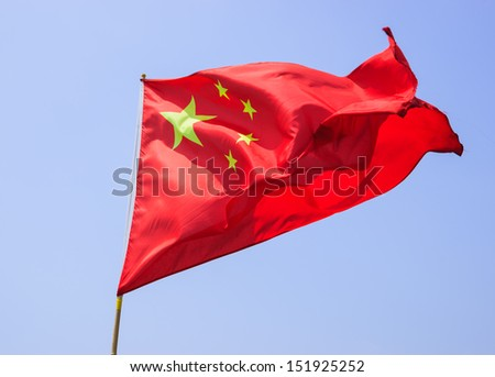 Chinese national flag against blue sky - stock photo