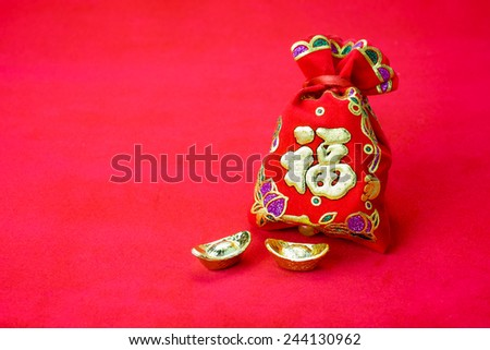 "Chinese new year decoration: red felt fabric bag or ang pow with word "" prosperous "" and golden ingots on red fabric - stock photo"