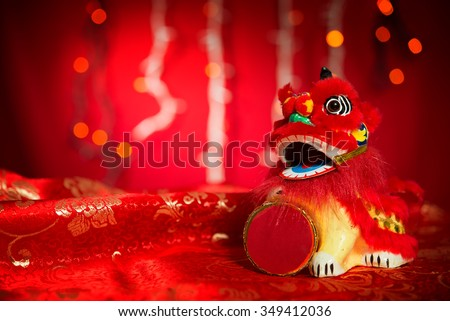 Chinese new year decorations, miniature dancing lion on red glitter background. - stock photo