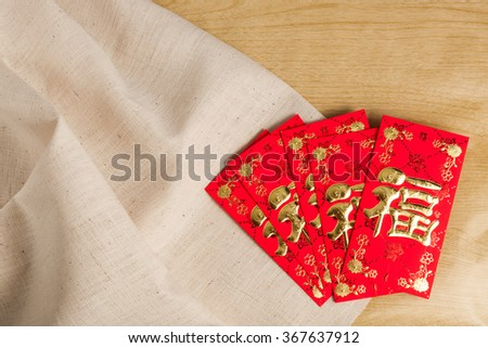 "Chinese New Year Decorations red envelope on wood and gunny sack (Foreign text means fortune"" or ""good luck) - stock photo"