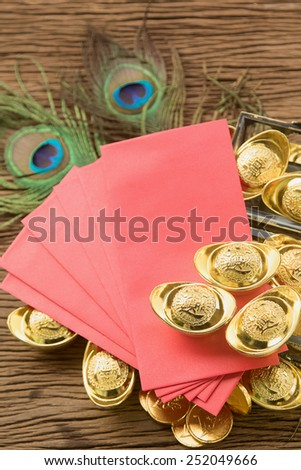 Chinese new year festival decorations, ang pow or red packet and gold ingots. - stock photo