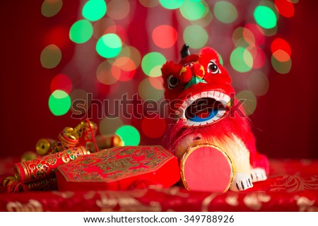 Chinese new year festival decorations, miniature dancing lion and firecrackers on red glitter background. - stock photo