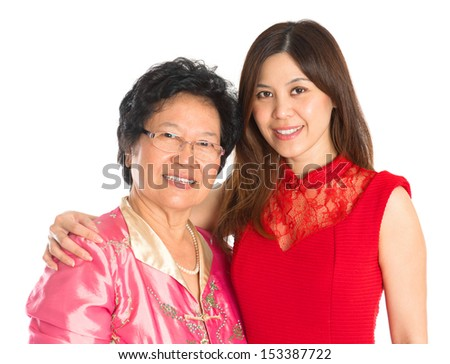 Chinese New Year festival. Happy Asian Chinese senior mother and adult daughter standing isolated on white background - stock photo