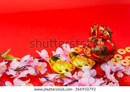 Chinese new year ornament. Gold ingots, red felt fabric bag or ang pow and copper coins - stock photo