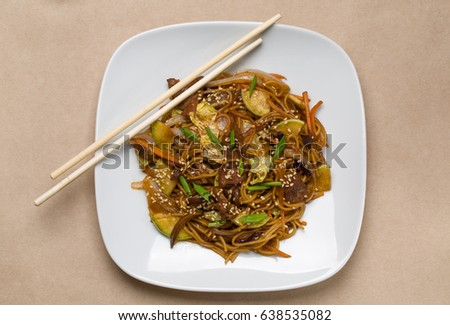 Chinese noodles with beef on a white plate in a restaurant