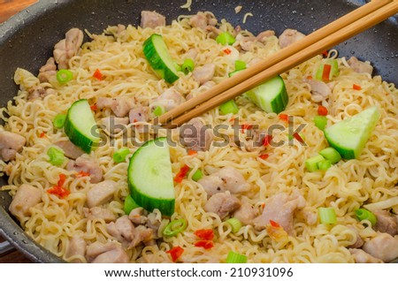 Chinese noodles with chicken on pan and wood table