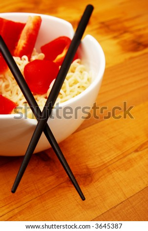 Chinese noodles with chop sticks in a bowl on wooden counter with some peppers in the noodles - stock photo