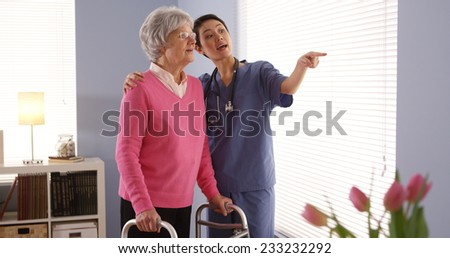 Chinese nurse and elderly woman patient looking out window