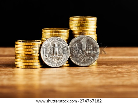 Chinese One Yuan Coin and us quarter dollar coin and gold money on the desk - stock photo